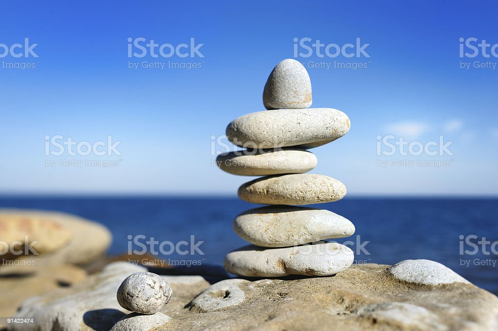 Stack of balancing pebbles with the sea in the background stock photo