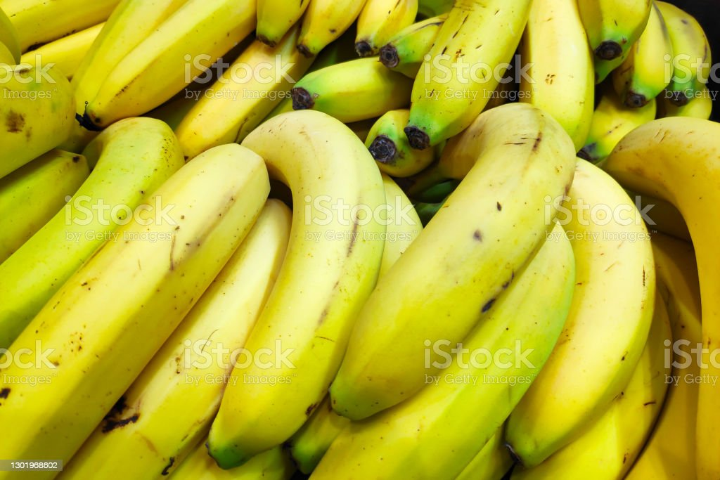 Stack of bananas on a market stall Close-up on a stack of bananas on a market stall. Abundance Stock Photo