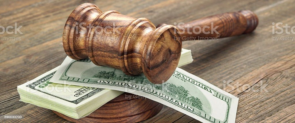 Stack Of Banknotes With Judges Or Auctioneers Gavel Or Hammer stock photo
