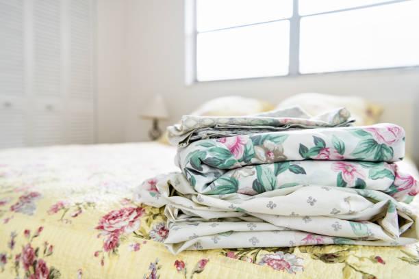 퀼트, 누비이 불,이 불, 밝은 자연 채광 창에서 침대 위에 꽃, 꽃 패턴으로 침실 리넨의 스택 램프, 백그라운드에서 옷장 - 침구 뉴스 사진 이미지