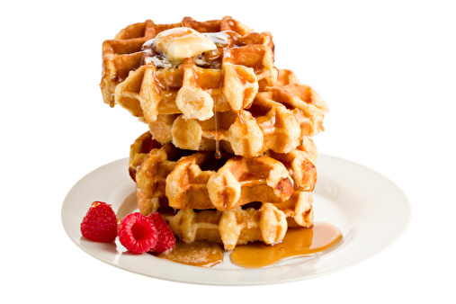 A stack of four Belgian waffles and three luscious red raspberries on a white plate with a melting slab of butter and maple syrup still barely trickling onto the butter. Isolated on white