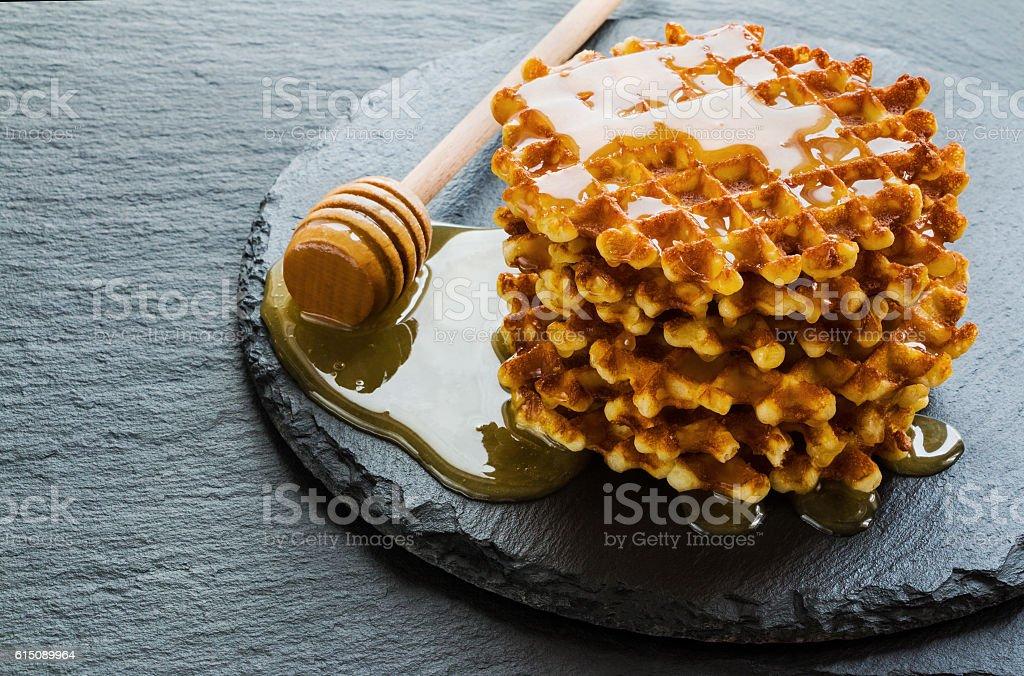 Stack of belgian waffles with honey on black stone background. - Photo