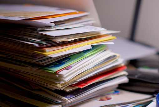 Large stack of financial bills, letters, cards, and advertisements on a home office desk, waiting to be opened.