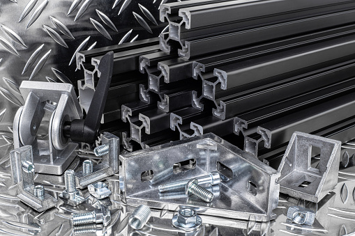 istock stack of black anodized aluminum extrusion bars, connector, joint, screw , slot nut and angle bracket silver shiny diamond plate background. Construction metal steel factory concept. 1169552114