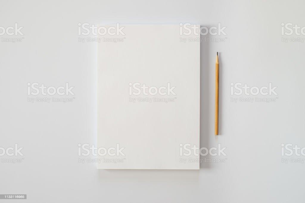 Una pila de hojas de papel en blanco y un lápiz sobre un fondo blanco. Crisis creativa o el comienzo de una nueva novela. foto de stock libre de derechos
