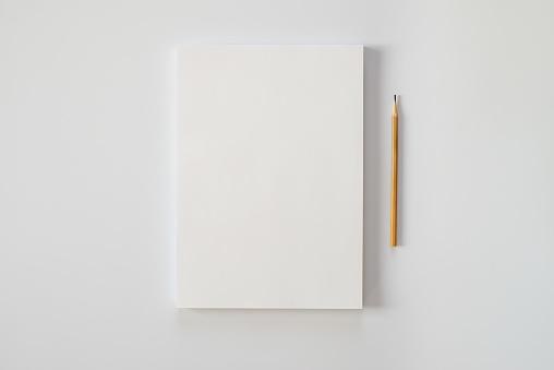 A stack of blank sheets of paper and a pencil on a white background. Creative crisis or the beginning of a new novel.