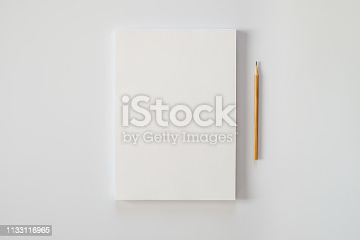 istock A stack of blank sheets of paper and a pencil on a white background. Creative crisis or the beginning of a new novel. 1133116965