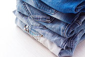 Stack of Blue jeans on white background, closeup
