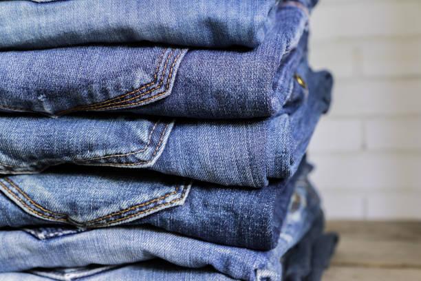 木架子上的藍色牛仔褲疊。美容和時尚服裝概念 - 牛仔褲 個照片及圖片檔