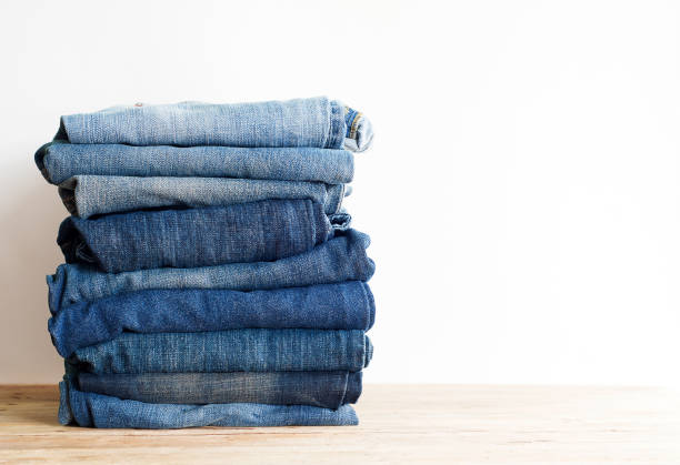 stack of blue jeans. - jeans stock photos and pictures