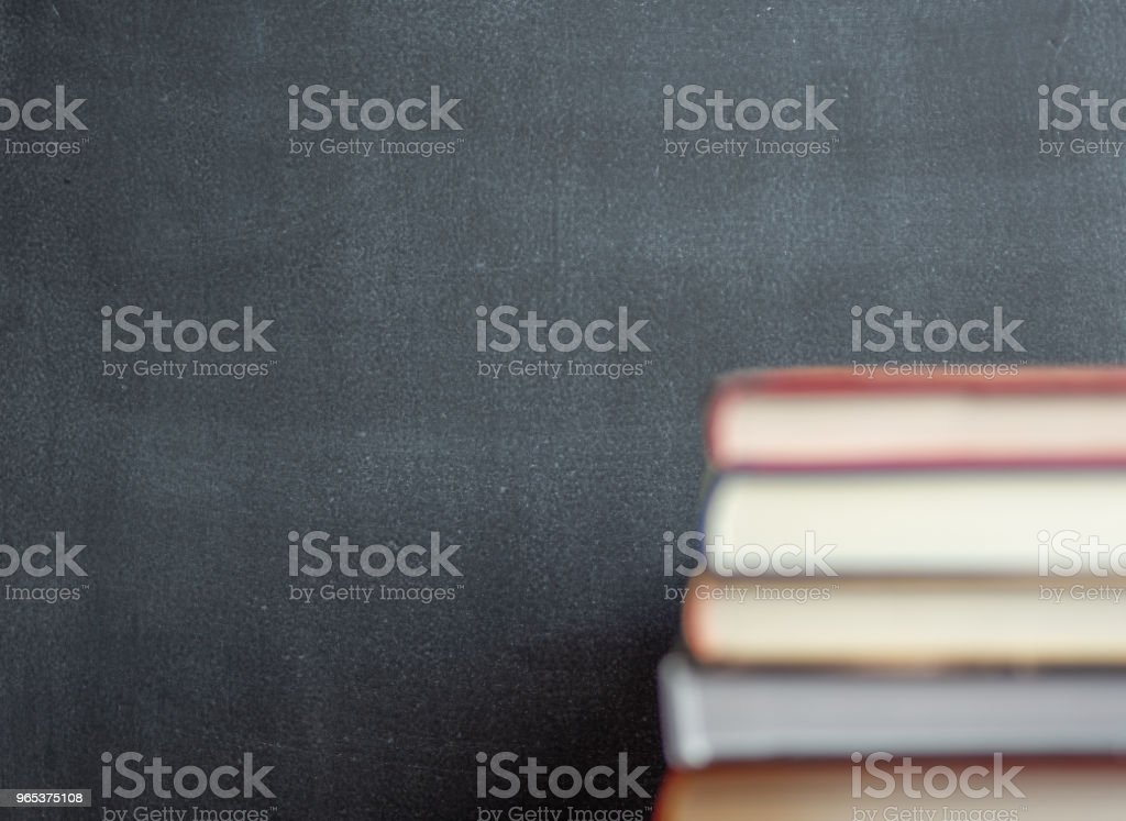 Stack of book resting in front of a chalkboard royalty-free stock photo