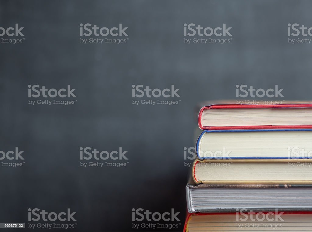 Stack of book resting in front of a chalkboard zbiór zdjęć royalty-free