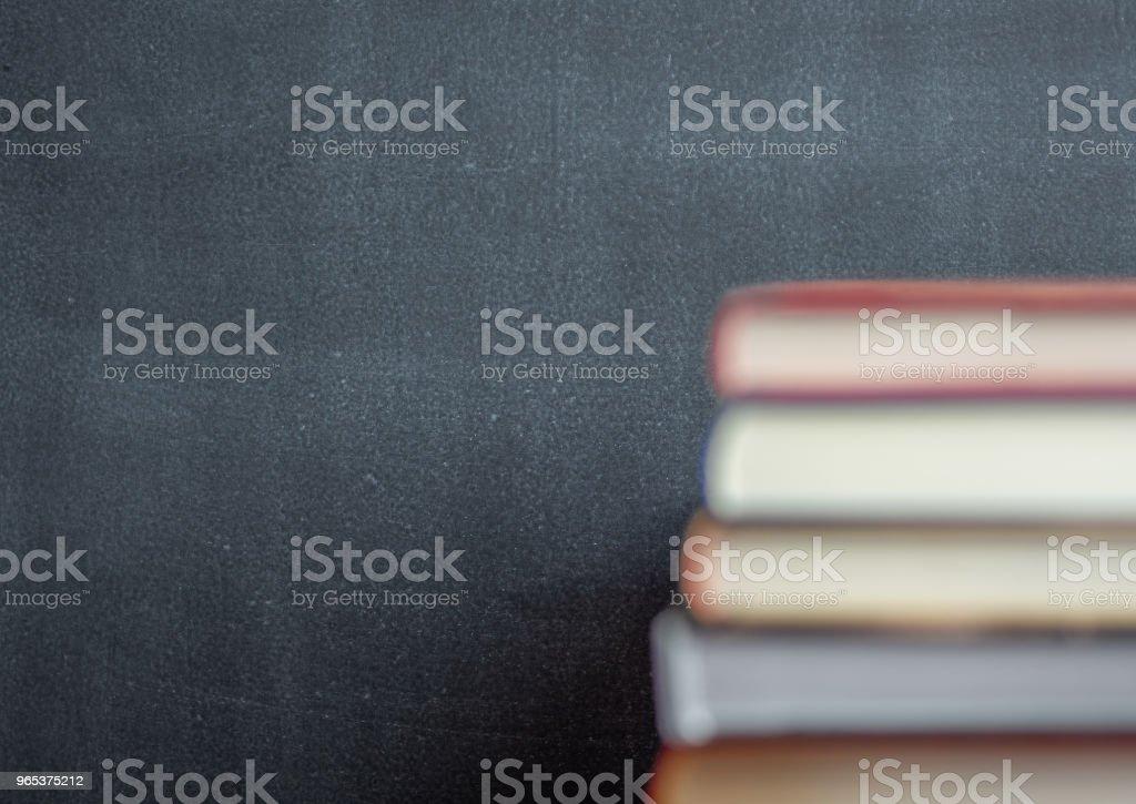Stapel von Buch ruht vor einer Tafel - Lizenzfrei Akademisches Lernen Stock-Foto