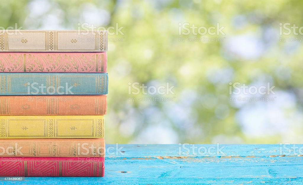stack of books against nature background stock photo