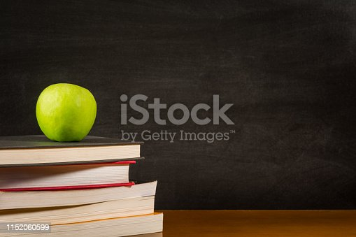 881192038 istock photo Stack of books and a green apple on a desk front of a blank blackboard 1152060599