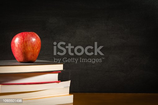 881192038 istock photo Stack of books and a red apple on a desk front of a blank blackboard 1093501498