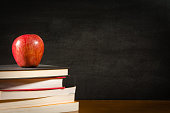 Stack of books and a red apple on a desk front of a blank blackboard
