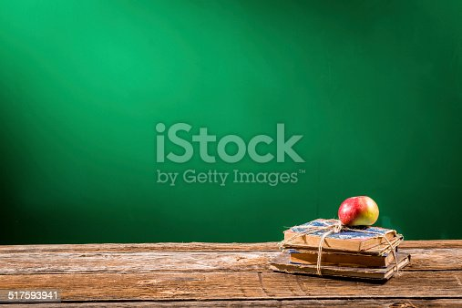 1045293630istockphoto Stack of books and an apple in a classroom 517593941