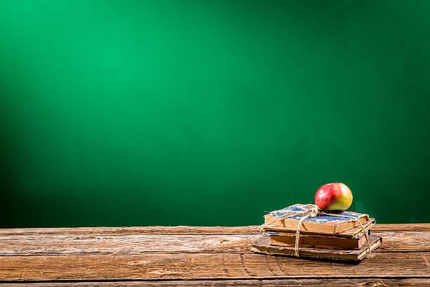 stapel von büchern und apple auf einem klassenzimmer - kreide farbe schreibtisch stock-fotos und bilder
