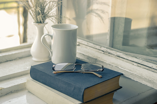 istock A stack of books and glasses on a window. A cup of coffee. 991984008