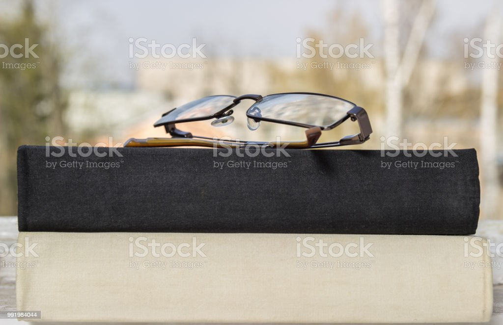A stack of books and glasses on a window. stock photo