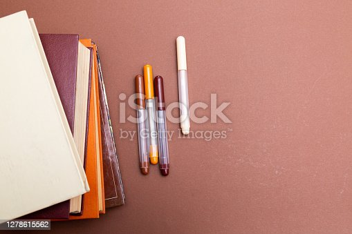A stack of books and multi-colored pens on a beige background. Business training concept. Home Office
