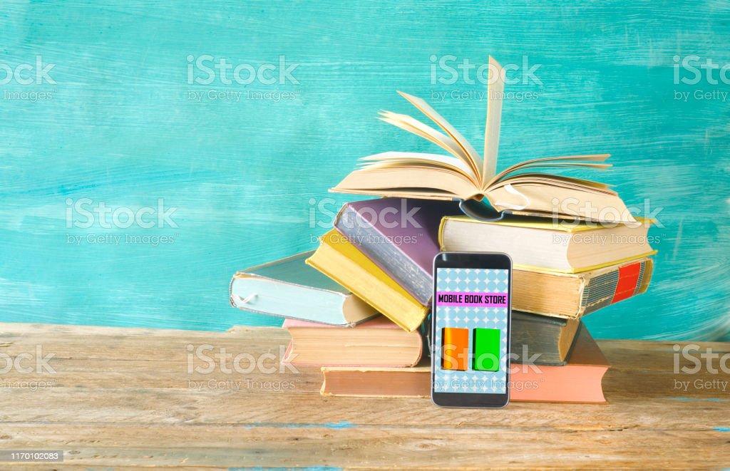 Stack of books and smartphone. online book shop, E- Book, book fair,...