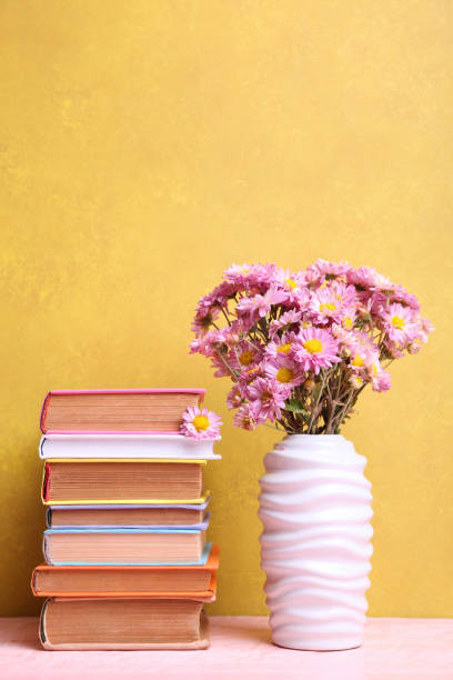 Stack of books and vase with bouquet of chrysanthemums stock photo