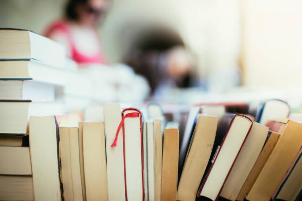 stack of books at a charity book flea market, text space - книга стоковые фото и изображения