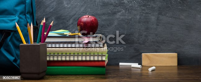 istock Stack of books, colorful stationery and education supplies on wooden table 905028982