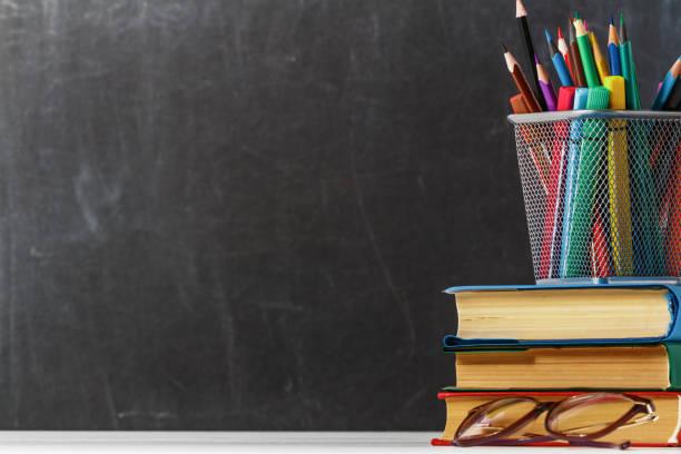 uma pilha de livros, vidros, lápis no fundo de uma placa de escola preta. o conceito de educação. copie o espaço. - professor - fotografias e filmes do acervo