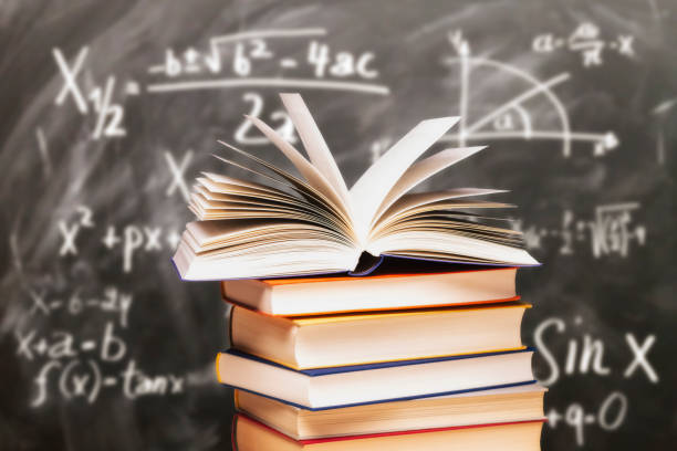 Stack of books in front of a blackboard stock photo
