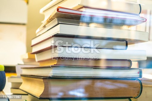 istock A stack of books in the library by the window 1126877397