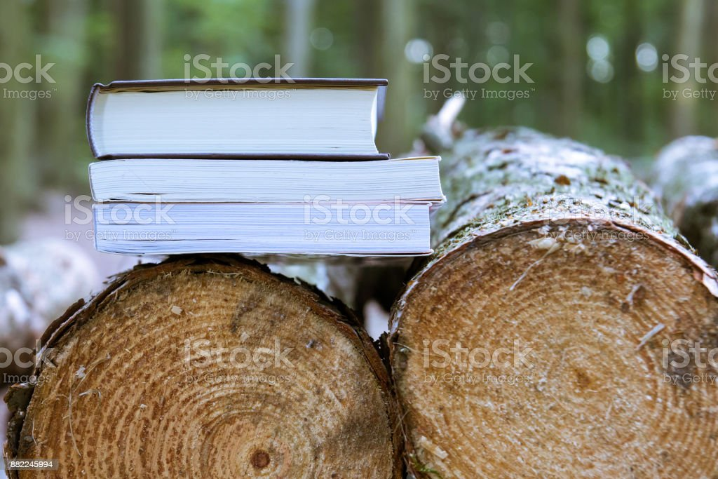 A stack of books lying on felled trees, save trees - read ebooks