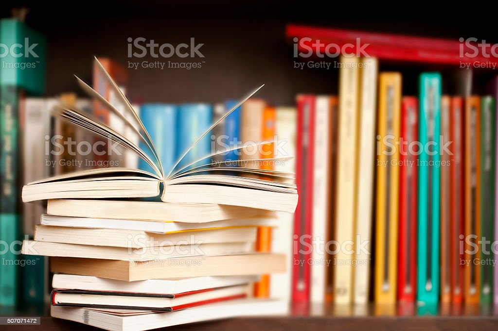 Stack of books on a shelf, multicolored book spines.