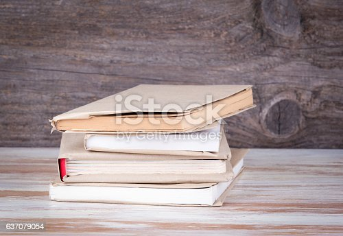 1034955096 istock photo Stack of books on a wooden table 637079054