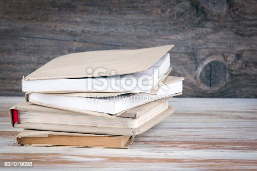 1034955096 istock photo Stack of books on a wooden table 637079098
