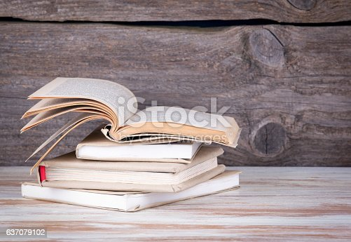 1034955096 istock photo Stack of books on a wooden table. 637079102
