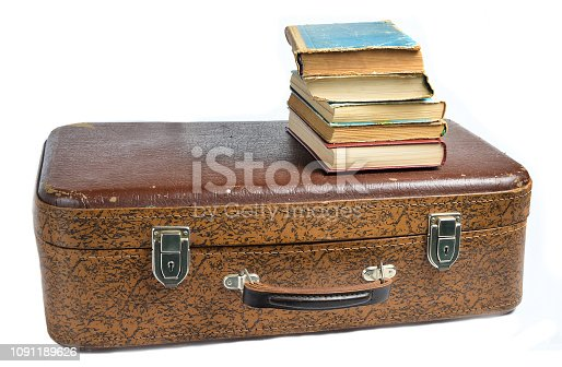 istock A stack of books on an old leather suitcase isolated on a white background. 1091189626