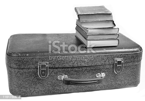 istock A stack of books on an old leather suitcase isolated on a white background. 1151730816