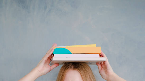 stack of books on female head. Cute and funny education concept. stock photo