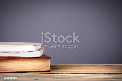 istock stack of books on grey background. Back to school with copy space 1034955096