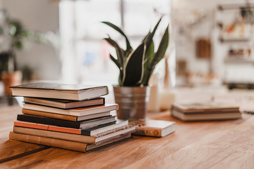 Stack of colorful books on wooden table in the room. Selective focus.