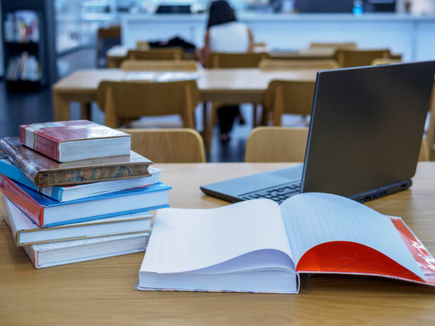 Stack of books on table top in the library / Education & Back to school concept stock photo
