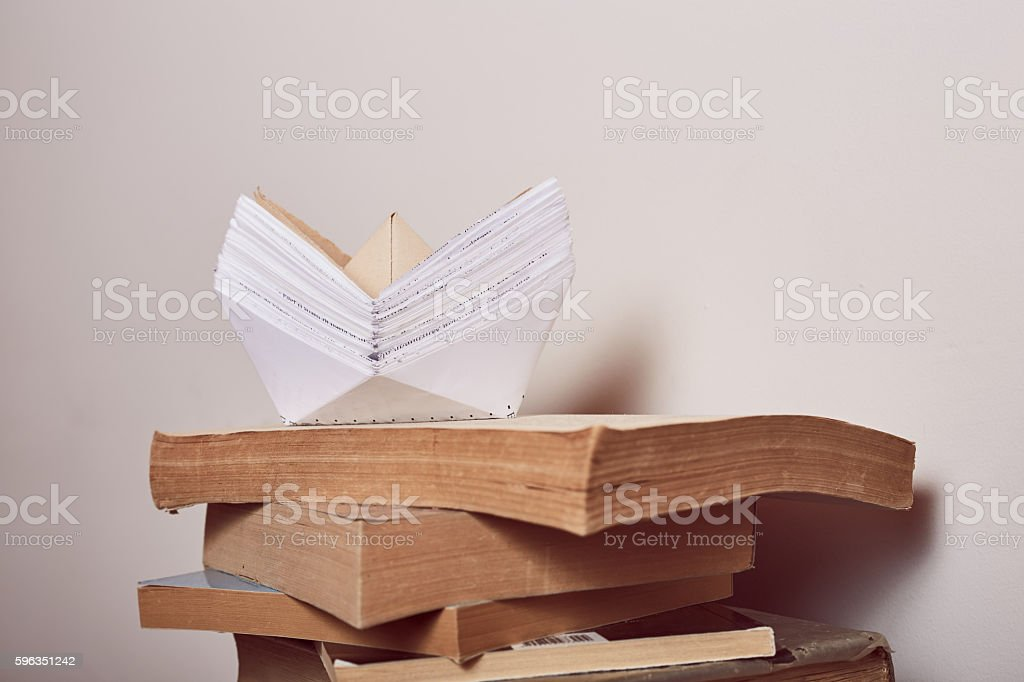 Stack of books on the paper boat royalty-free stock photo