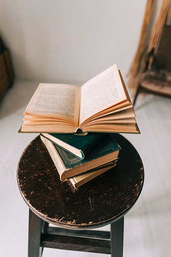 Close up image of open notebook with old books in the back.