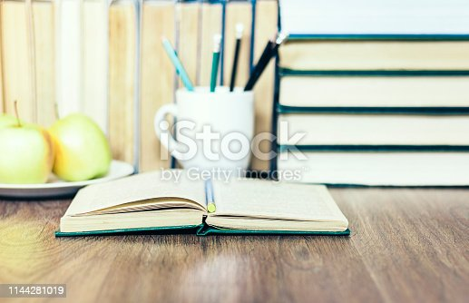 istock Stack of books, open book, glasses and green apples, background for education learning concept 1144281019