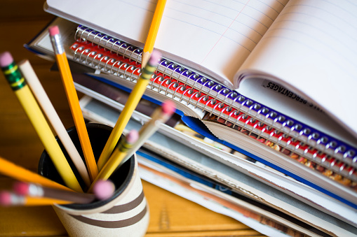 Stack of books or paperwork on desk. High angle view, pencils in holder in foreground.