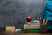 Stack of books, stationery and education supplies on wooden desk