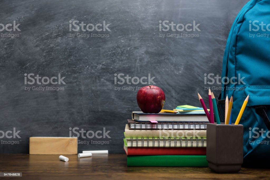 Stack of books, stationery and education supplies on wooden desk stock photo